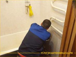 Сантехник осматривает ванну перед ее демонтажем